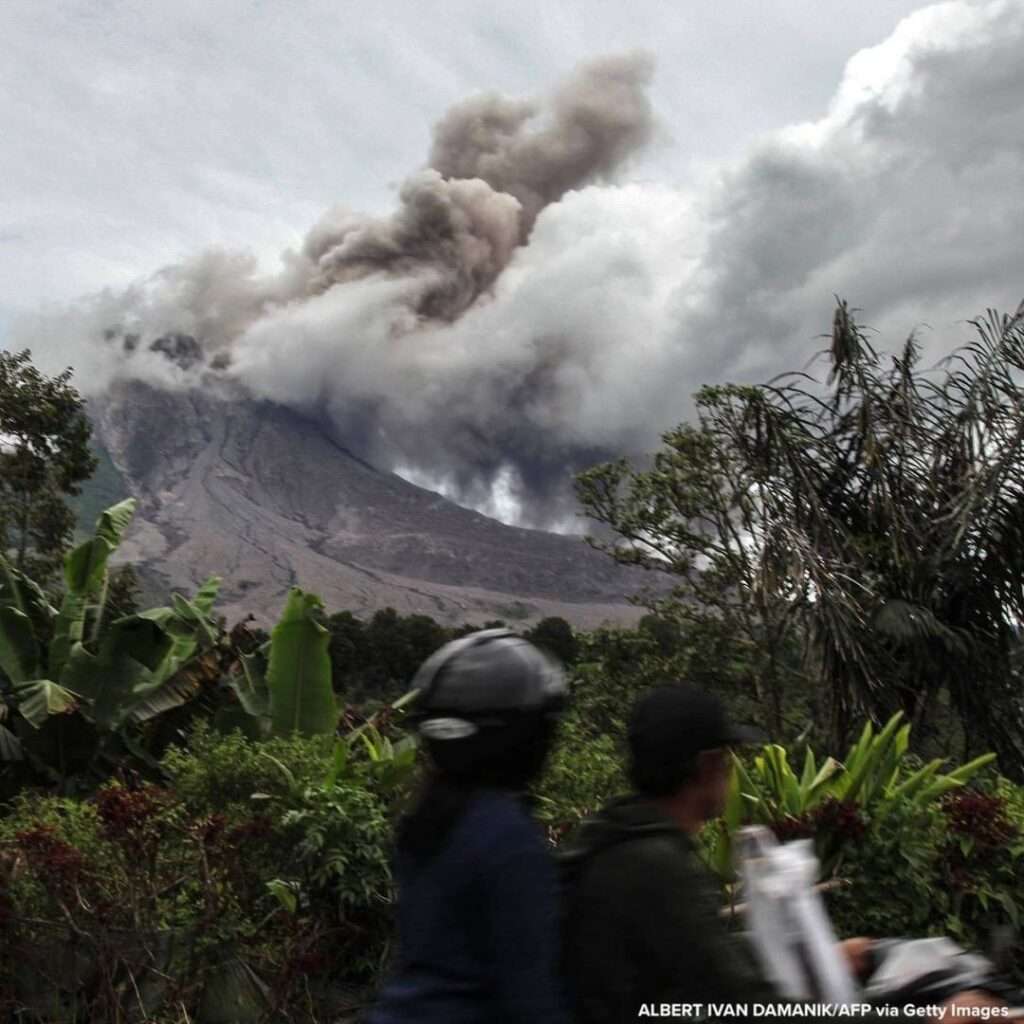 Motorist passes by as Mount Sinabung volcano spews thick smoke into the air in K...