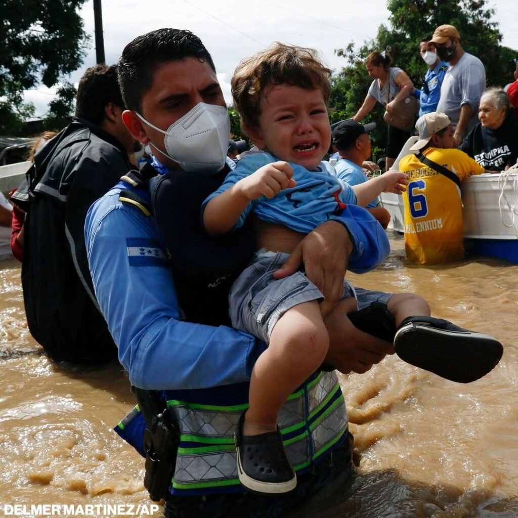 A toddler is carried through a flooded street in Honduras amid deadly flooding a...