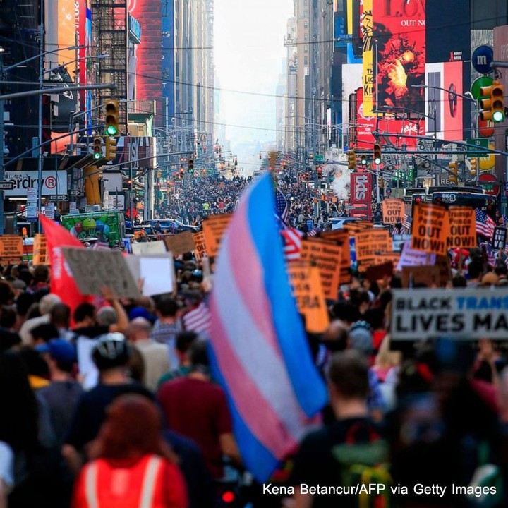 People march down 7th Avenue in New York City, stretching as far as the eye can ...