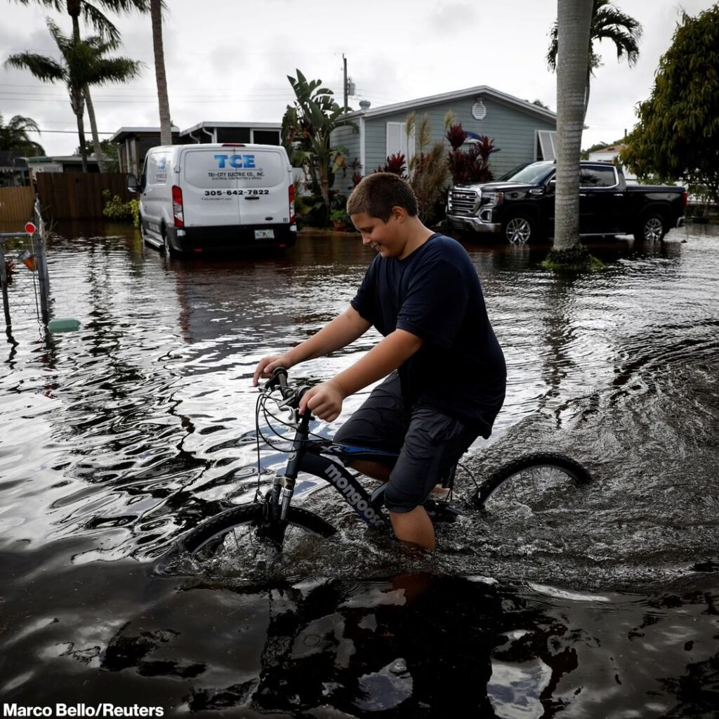 A boy attempts to ride his bicycle through floodwaters caused by Tropical Storm ...