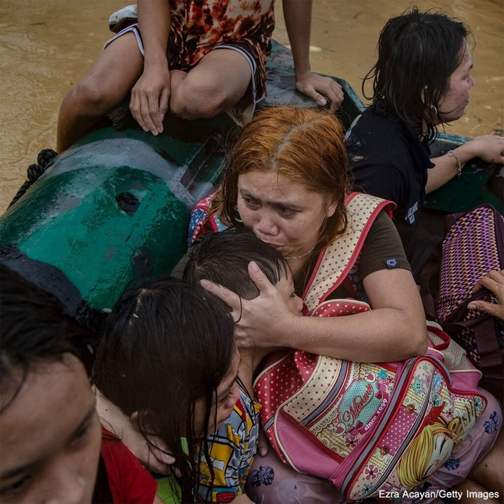 Residents of Rodriguez, Rizal province, Philippines, huddle close in a rubber bo...