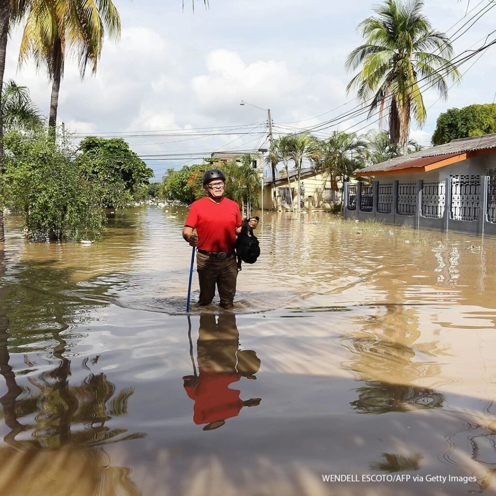 A man wades through the water in the flooded municipality of La Lima near San Pe...
