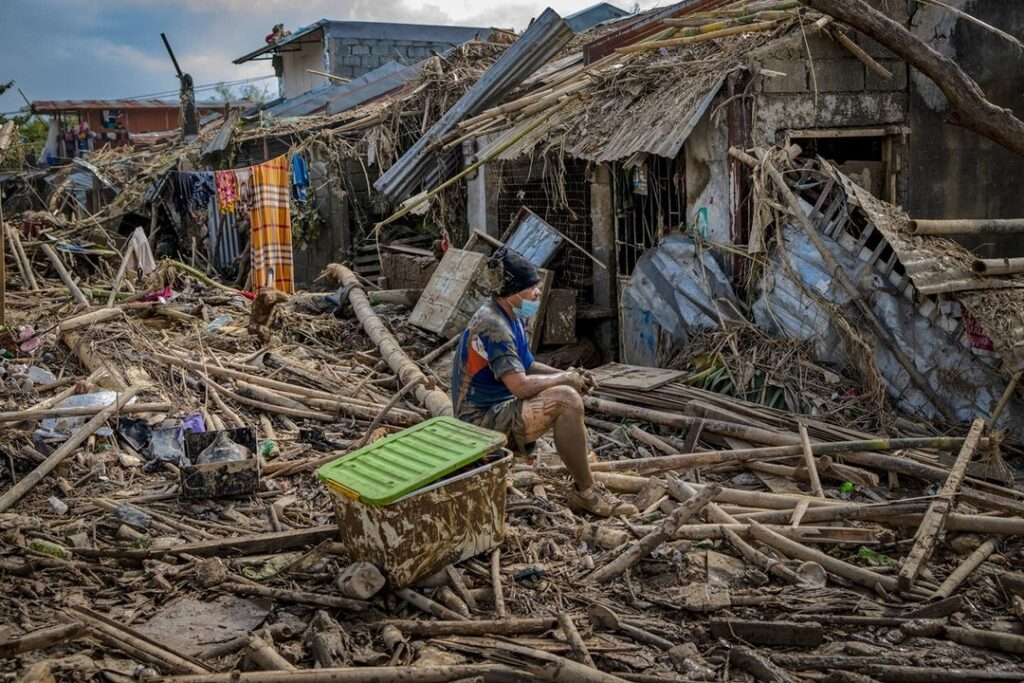 A resident sits outside destroyed houses after Typhoon Vamco hit Rodriguez, Riza...