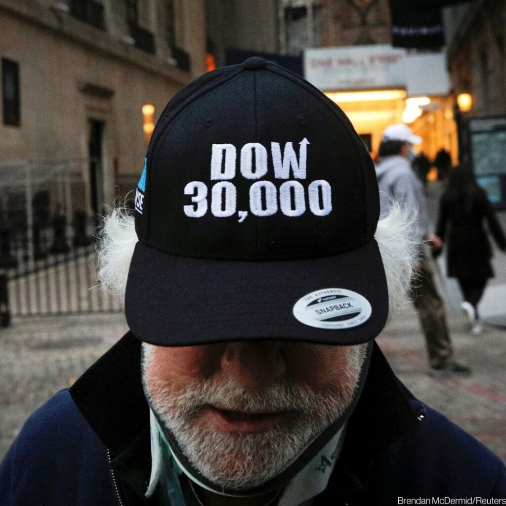 """Trader Peter Tuchman wears a """"DOW 30,000"""" hat as he greets friends outside the N..."""